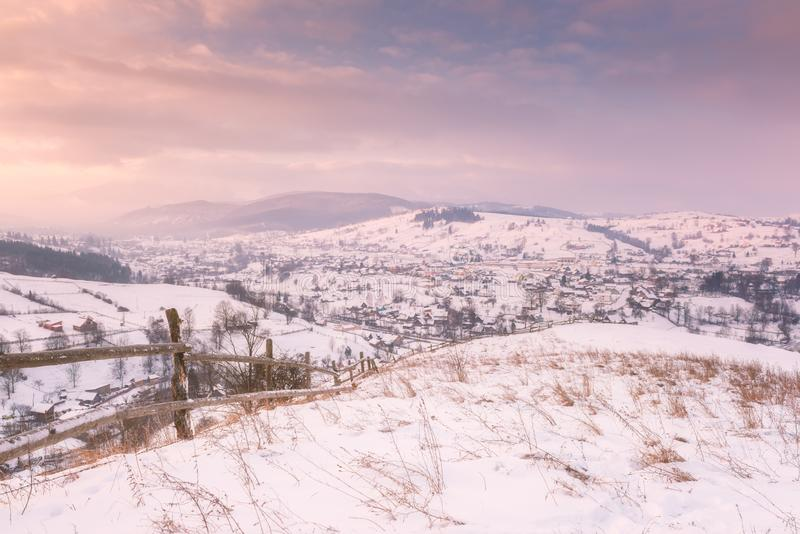 Beautiful winter landscape in soft sunset light, alpine valley surrounded by wooded mountains stock photo