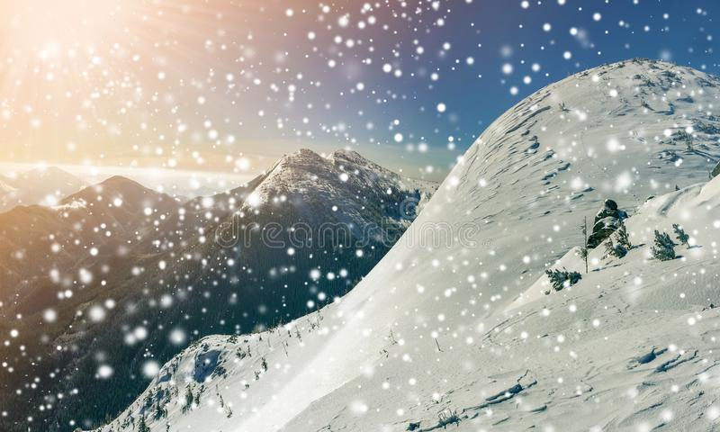 Beautiful winter landscape. Steep mountain hill slope with white deep snow, distant mountain range panorama, large snowflakes and. Bright shining sun rays on stock image