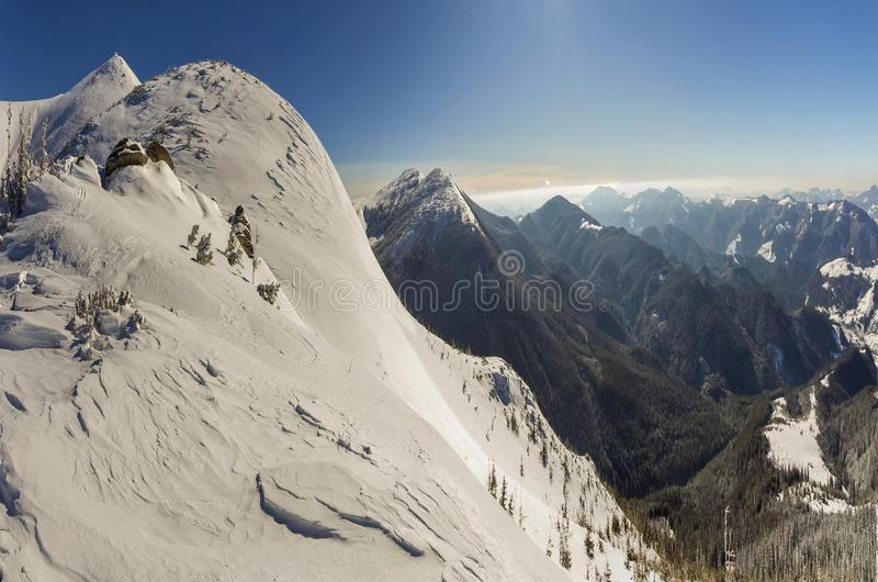 Beautiful winter landscape. Steep mountain hill slope with white deep snow, distant woody mountain range panorama stretching to. Horizon and bright shining sun royalty free stock images