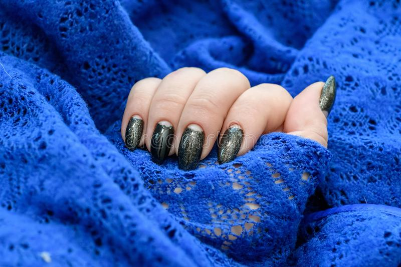 Beautiful winter manicure. Black lacquer with luster and white patterns of snow and frost. The blue background is also stock images