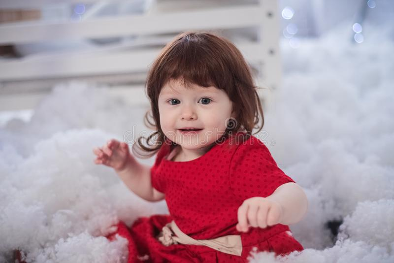 Beautiful winter portrait of a charming chit. The happy childhood of the little girl in a red dress royalty free stock photography