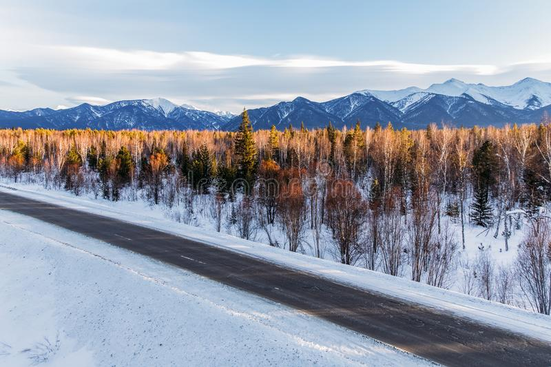 Beautiful winter road with trees and snow covered mountains,. Russian federation stock photography