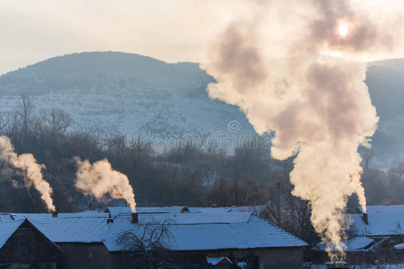 Beautiful winter scenery with smoke coming from house chimneys, on a bright, cold, morning, in remote countryside in Europe. Beautiful winter scenery with smoke stock photo
