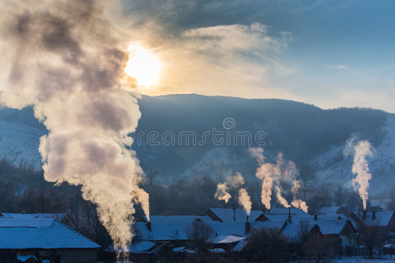Beautiful winter scenery with smoke coming from house chimneys, on a bright, cold, morning, in remote countryside in Europe. Beautiful winter scenery with smoke stock photography