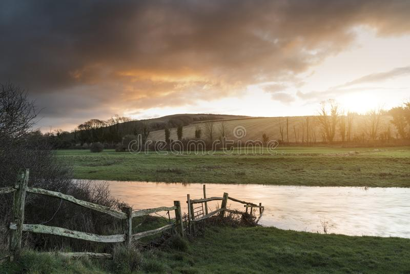 Beautiful Winter sunrise landscape of Cuckmere River winding through South Downs countryside in England stock photography