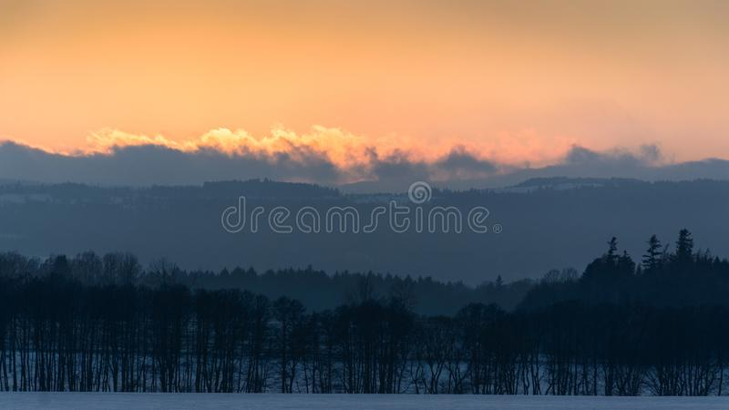 Beautiful Winter sunset in the mountain valley. Winter sunset in the mountain valley europe poland sudety peaks mountains forest trees clouds snow end day royalty free stock images