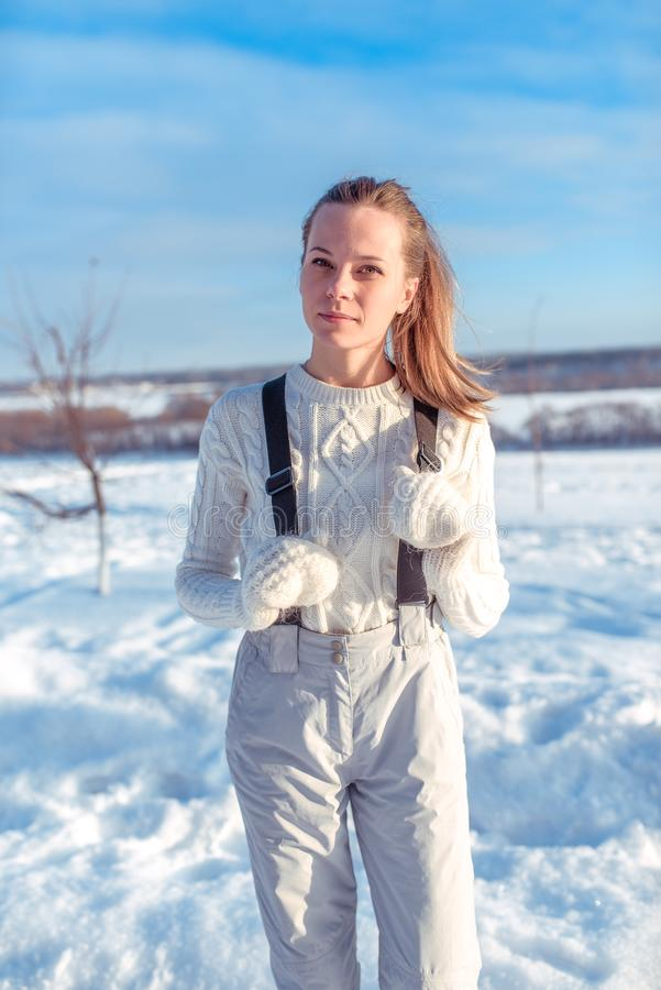 Beautiful winter woman in white jumpsuit and warm mittens. Posing in the city against the backdrop of snow and snow royalty free stock photos