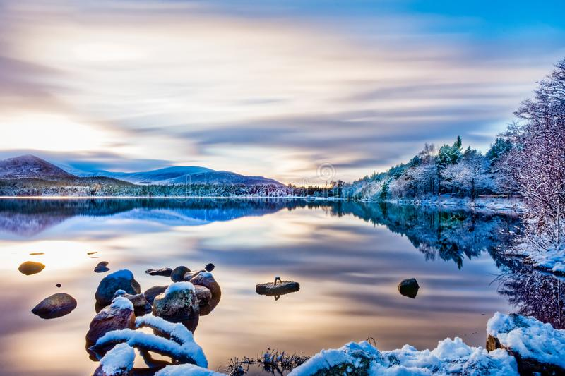 Beautiful winters day with soft clouds, snow on trees and rocks, reflections on calm water at Loch Morlich stock image