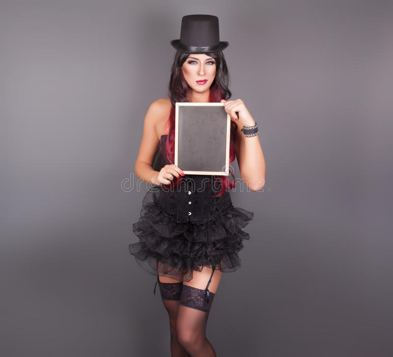 Beautiful witch in black gothic Halloween costume. Holding blackboard in hands royalty free stock photo