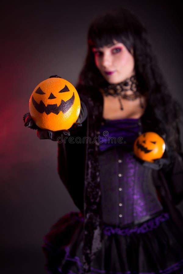 Beautiful witch holding Jack lantern oranges stock image