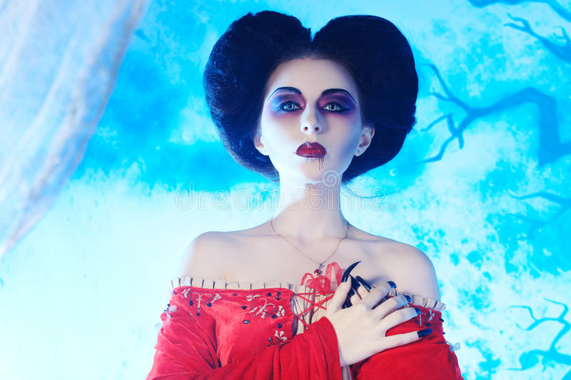 Beautiful witch. Portrait of a beautiful female vampire over moonlight background stock images