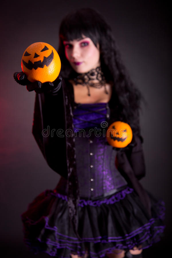 Beautiful witch in purple gothic Halloween costume. With Jack lantern oranges, selective focus on fruits royalty free stock photo