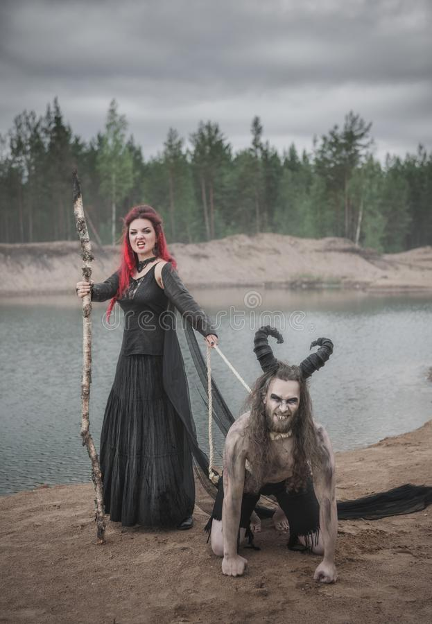 Beautiful witch with red hair and her horned demon royalty free stock photo