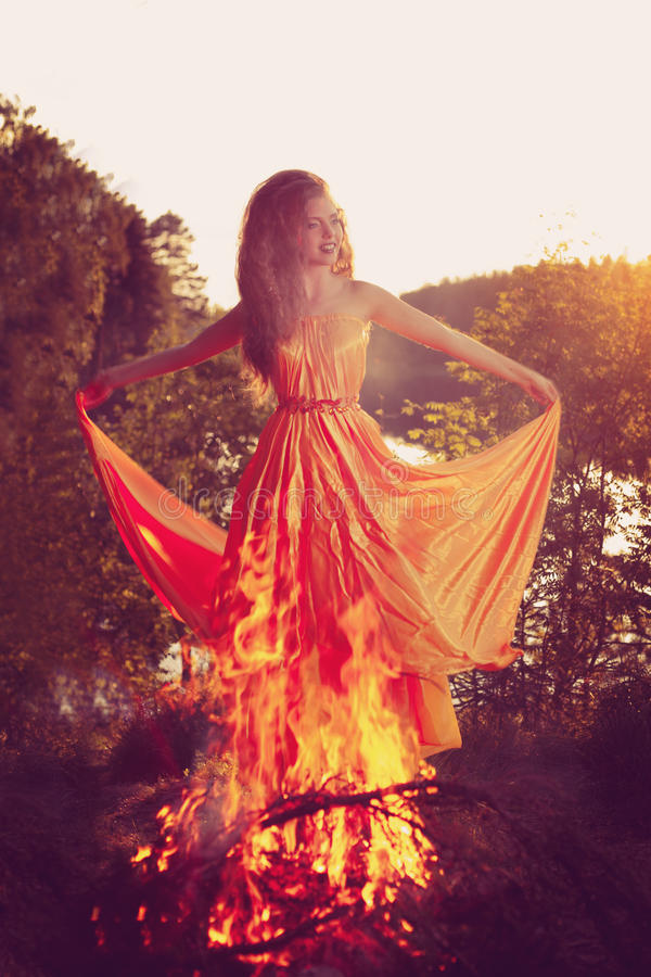 Beautiful witch in the woods near the fire. Magic woman celebrating Halloween. Girl doing witchcraft in the forest. royalty free stock photo