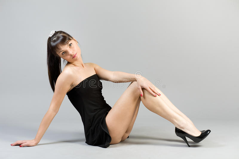 Beautiful woman. The girl in a short black dress sitting on a floor stock images