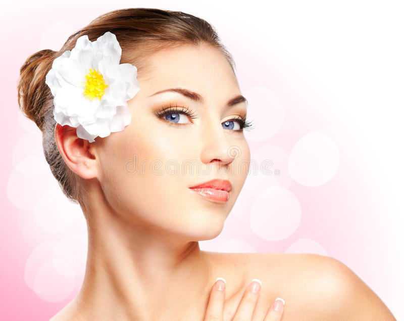 Beautiful woman. Closeup beautiful woman face with flower on white background royalty free stock images