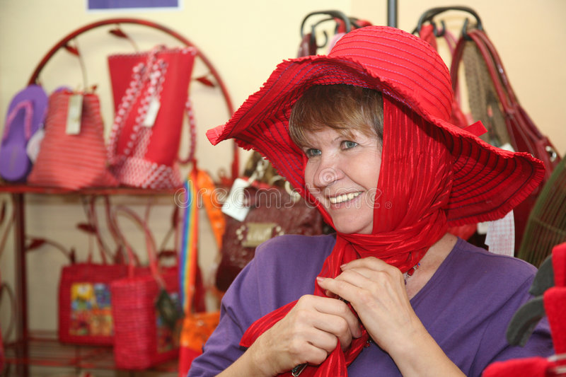 Beautiful woman. Beautiful senior caucasian society woman shopping for a red hat royalty free stock images