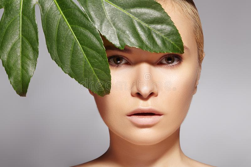 Beautiful woman applies Organic Cosmetic. Spa and Wellness. Model with Clean Skin. Healthcare. Picture with leaf royalty free stock photo
