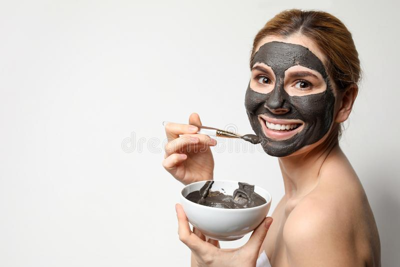 Beautiful woman applying black mask onto face against light background. Space for text stock photography