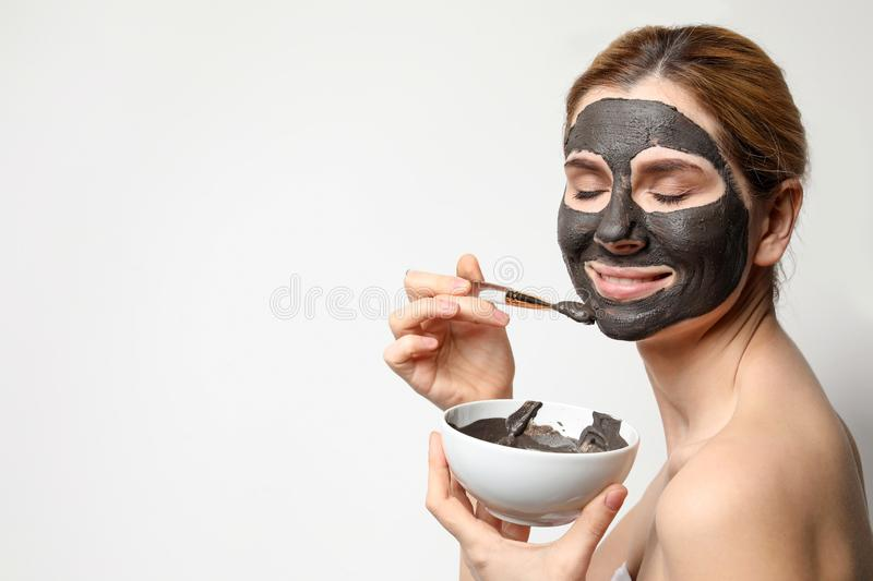 Beautiful woman applying black mask onto face against light background. Space for text royalty free stock photos