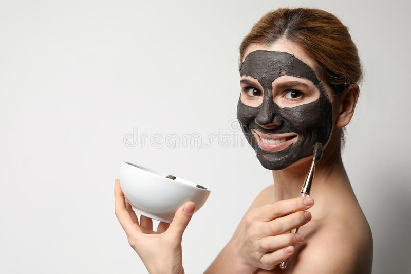 Beautiful woman applying black mask onto face against light background. Space for text royalty free stock image
