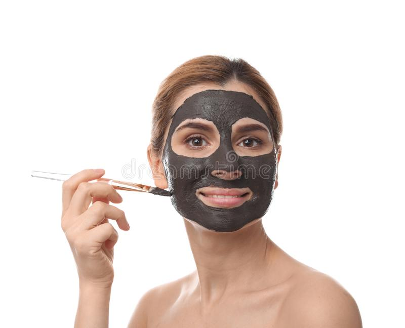 Beautiful woman applying black mask onto face. Against white background royalty free stock images