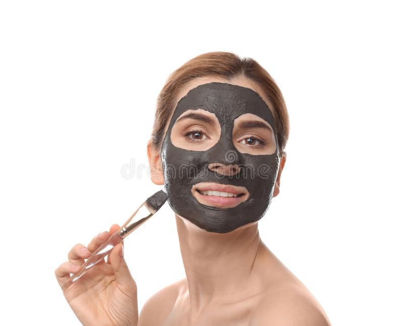 Beautiful woman applying black mask onto face. Against white background royalty free stock photo