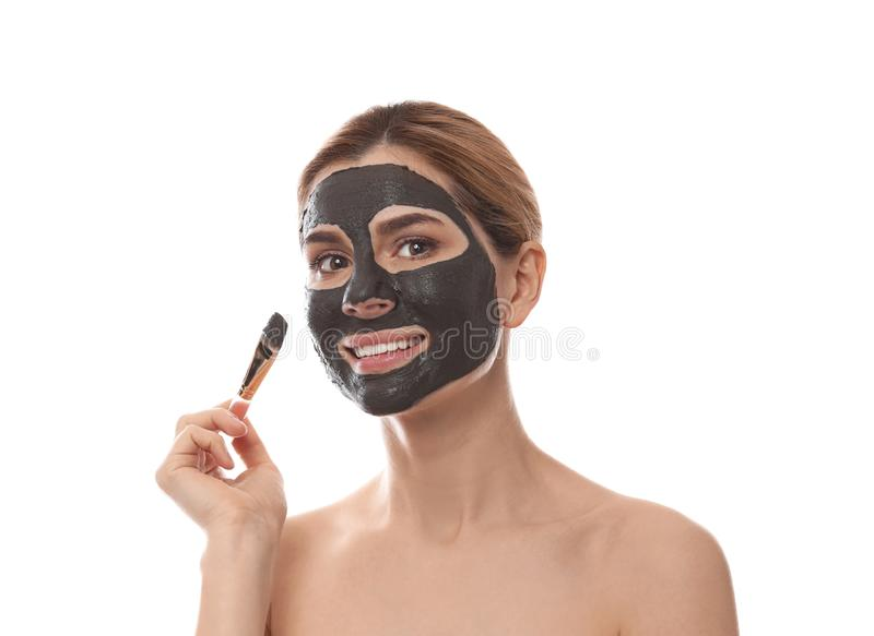 Beautiful woman applying black mask onto face. Against white background stock image