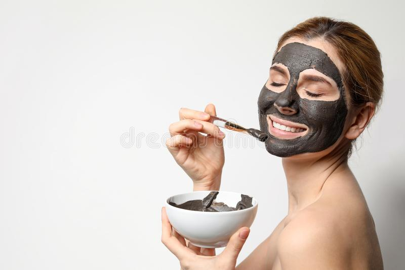 Beautiful woman applying black mask onto face. Space for text. Beautiful woman applying black mask onto face against light background. Space for text stock images