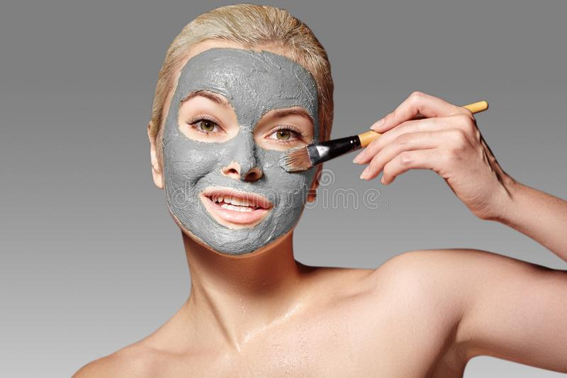 Beautiful Woman Applying Clay Facial Mask. Beauty Treatments. Spa Girl Apply Clay Facial mask with Beauty Brush royalty free stock photo