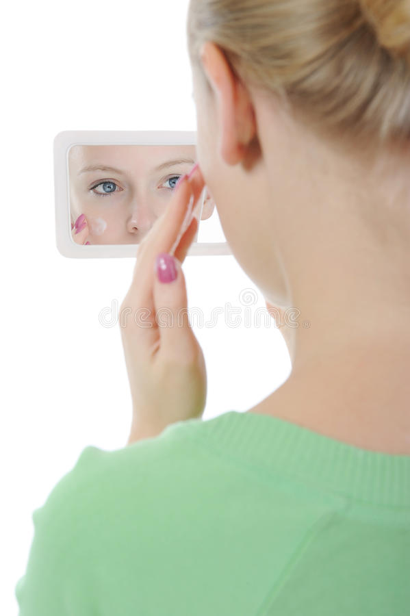 Beautiful woman applying cream on her cheek. Front of the mirror. Isolated on white background royalty free stock image