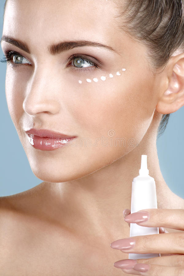 Beautiful woman applying cream treatment on her perfect face stock image