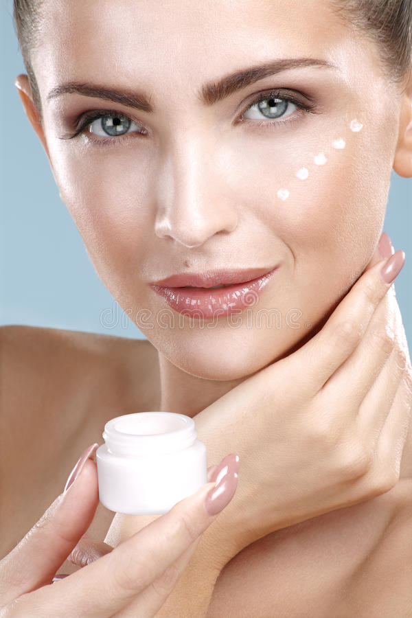 Beautiful woman applying cream treatment on her perfect face. On blue royalty free stock images
