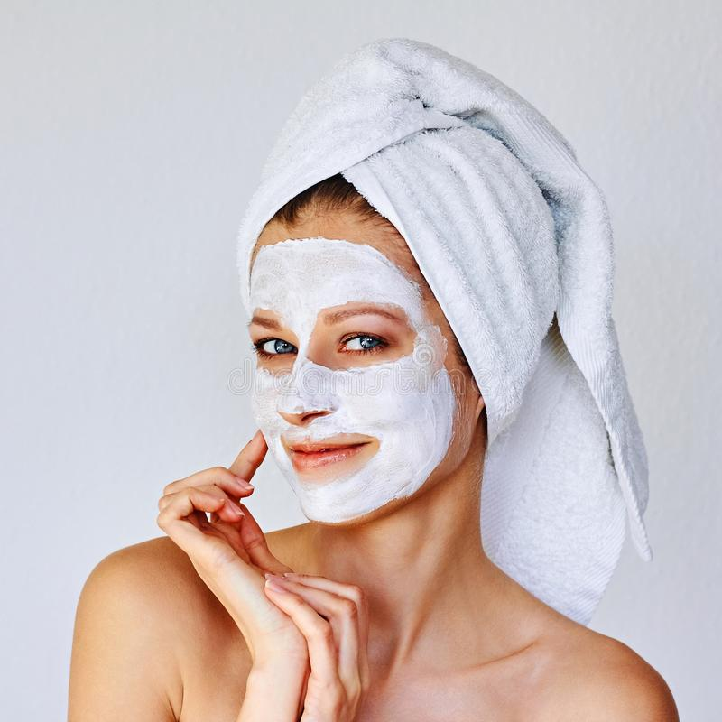Beautiful woman applying facial mask on her face. Skin care and treatment, spa, natural beauty and cosmetology concept royalty free stock image