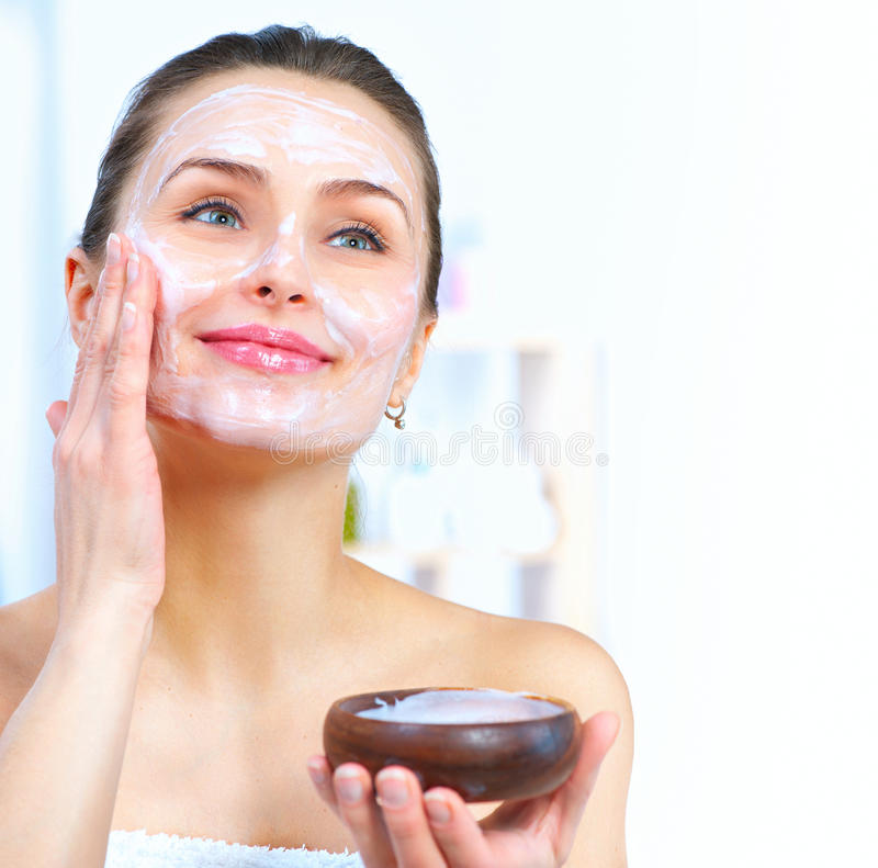 Beautiful woman applying facial mask. Beautiful woman applying natural facial mask royalty free stock photo