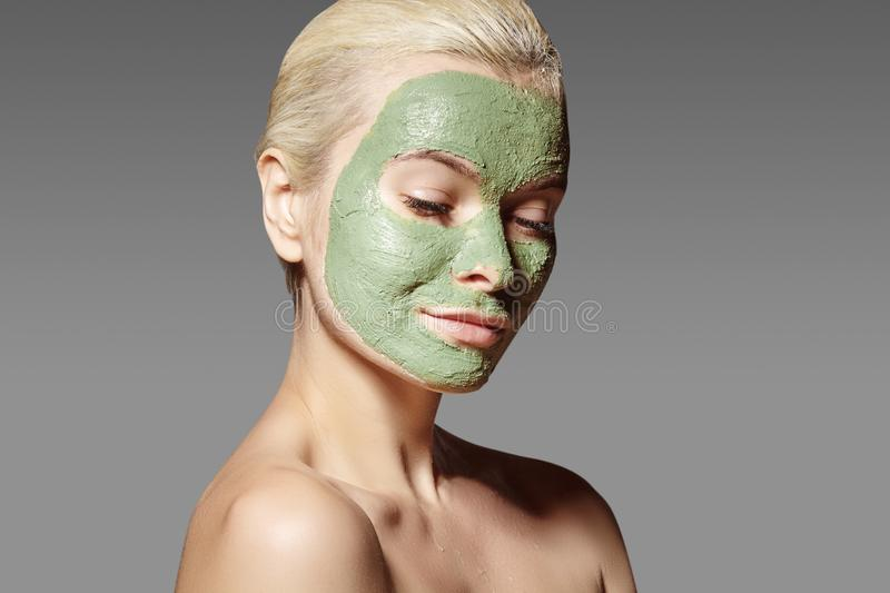Beautiful Woman Applying Green Facial Mask. Beauty Treatments. Spa Girl Apply Clay Facial mask on grey background royalty free stock photo