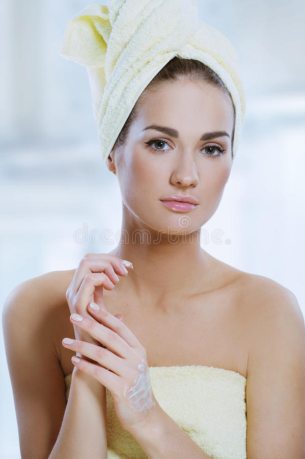 Beautiful woman applying hand cream. Beautiful woman with fresh healthy skin applying hand cream after bath. Spa woman concept royalty free stock image