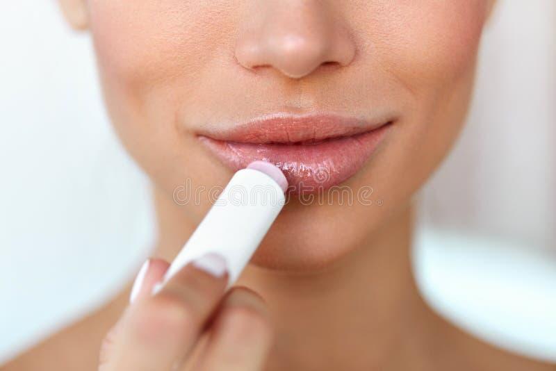 Beautiful Woman Applying Lip Protector On Lips Skin. Beauty stock images