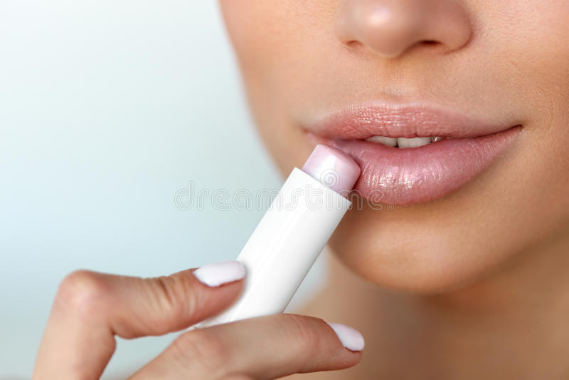 Beautiful Woman Applying Lip Protector On Lips Skin. Beauty. Lips Skin Care. Beautiful Woman Face With Full Lips Applying Hygienic Lip Balm, Lipcare Stick royalty free stock image