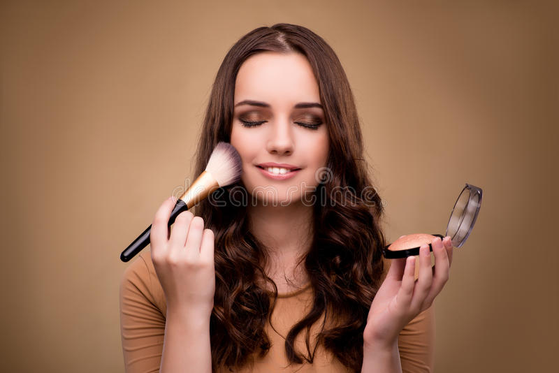 The beautiful woman applying make-up in beauty concept. Beautiful woman applying make-up in beauty concept royalty free stock images
