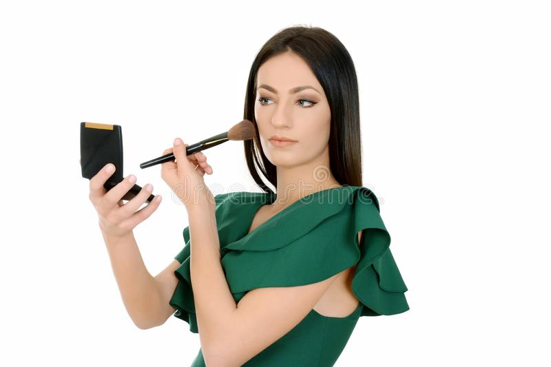 Beautiful woman applying make-up, holding make up brush and small mirror stock images