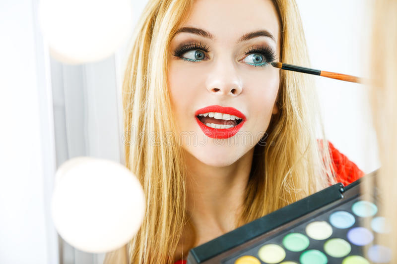 Beautiful Woman Applying Makeup at the Mirror royalty free stock photos