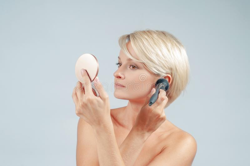 Beautiful woman applying makeup with powder brush on the face looking at a mirror stock photography