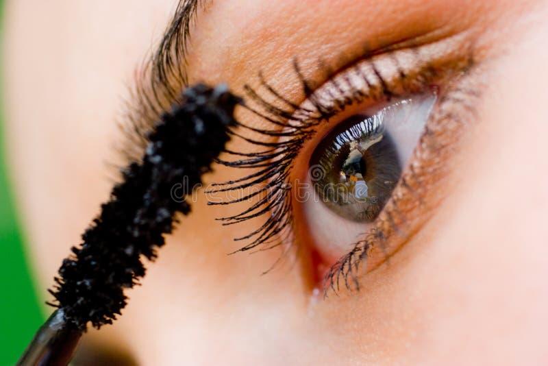 Beautiful woman applying mascara with brush royalty free stock photos