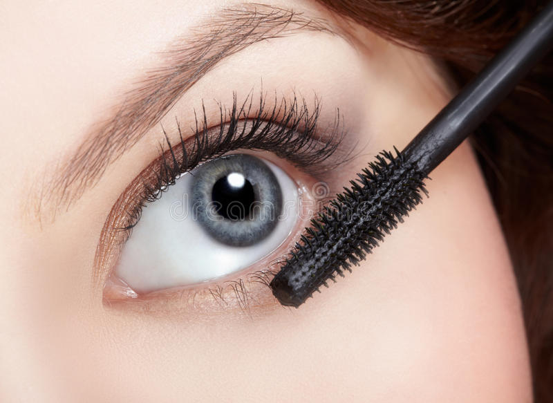 Beautiful woman applying mascara stock images