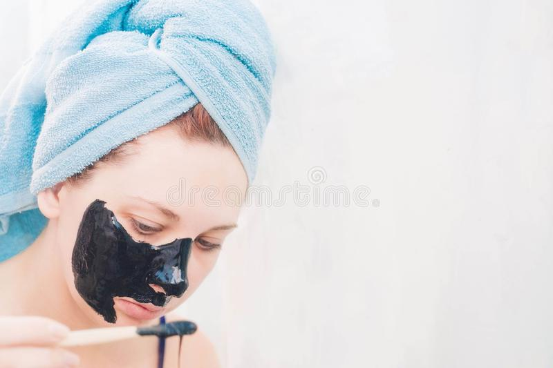 Black mask. Beautiful woman is applying purifying black mask on her face over white background royalty free stock images