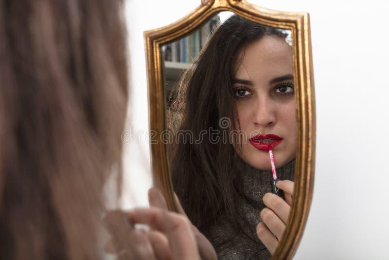 Beautiful woman applying red lipstick royalty free stock photos