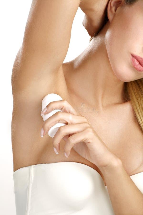Beautiful woman applying roll deodorant royalty free stock photos