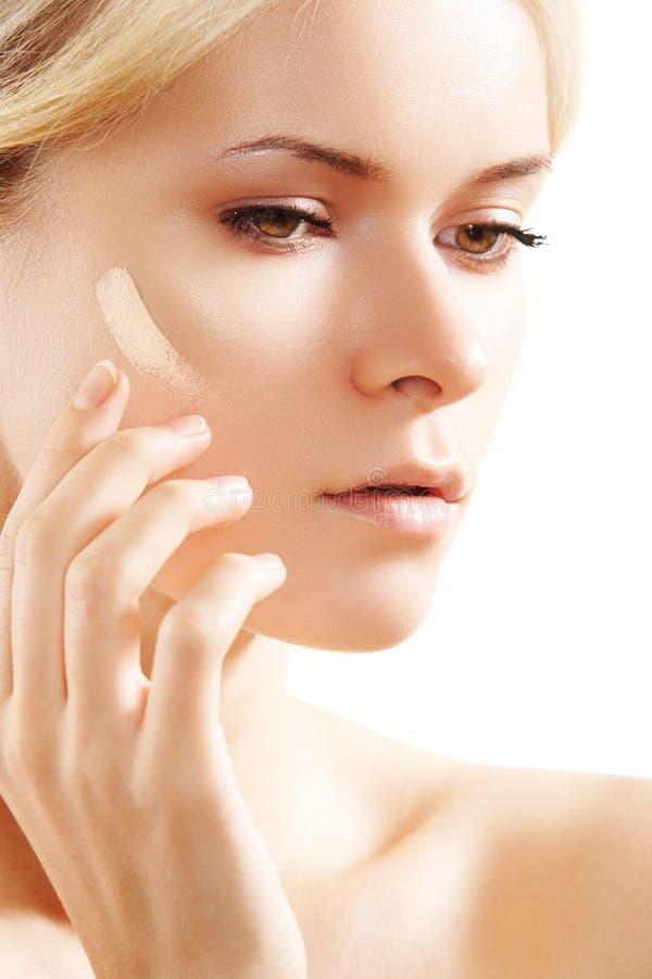 Beautiful woman applying skin tone cream on cheek