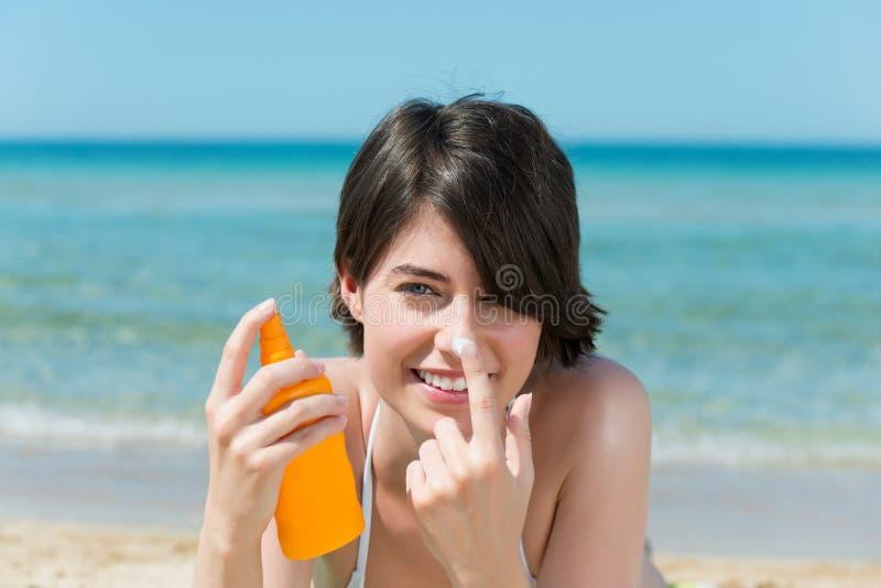 Beautiful woman applying sunscreen to her nose